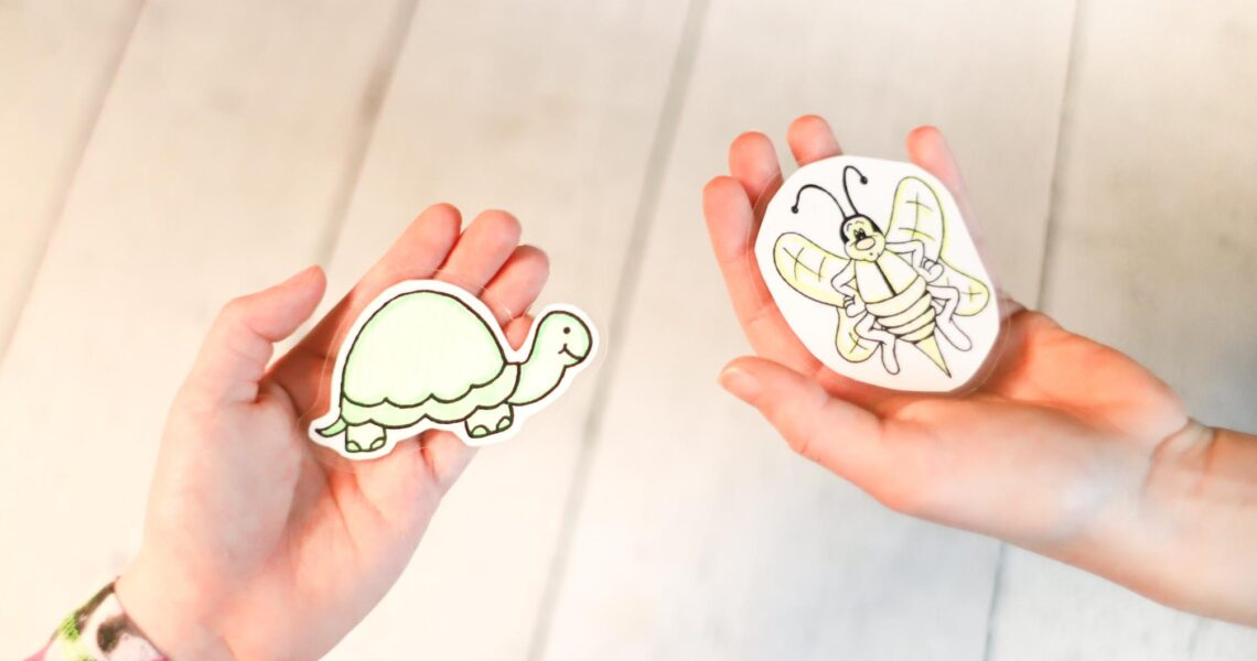One hand holding a turtle picture, one hand holding a bee picture for song time