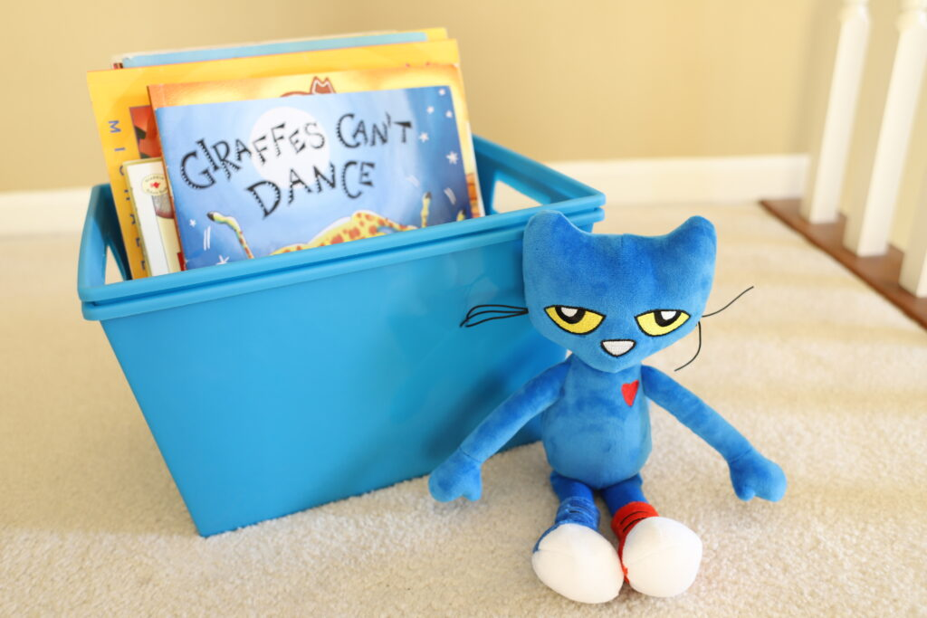 Pete the Cat next to plastic container holding picture books