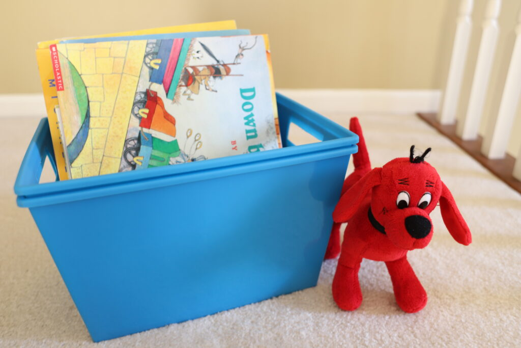 Stuffed Animal Clifford next to plastic storage container with paperback picture books