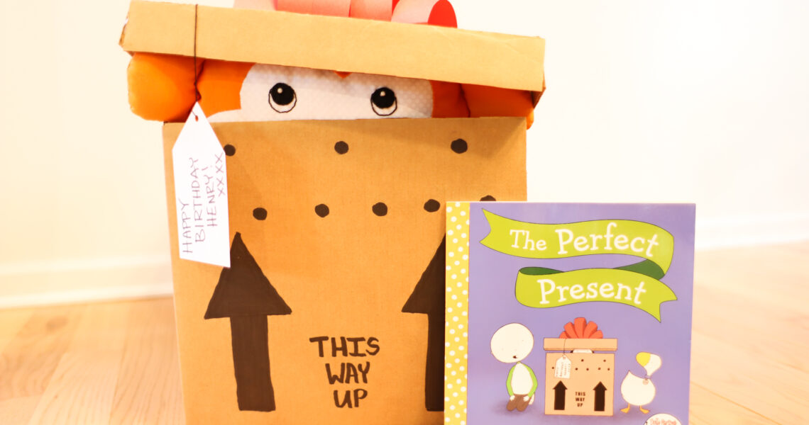 """Box with Monkey inside next to the book """"The Perfect Present"""""""