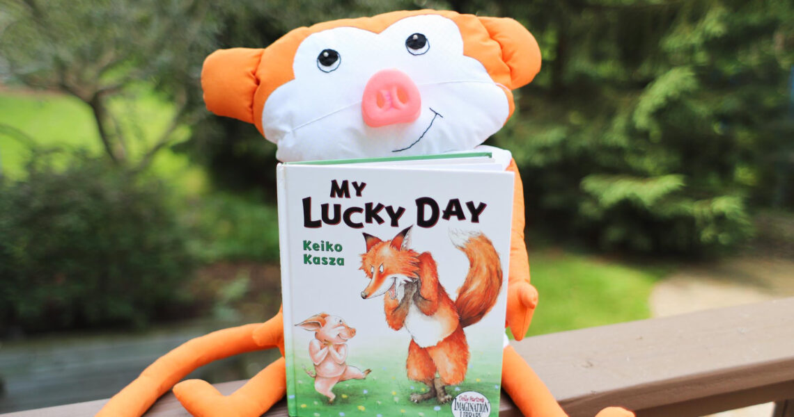 Monkey dressed in pig nose holding the picture book My Lucky Day