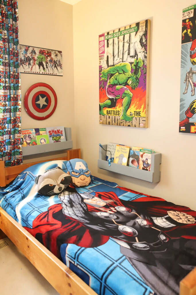 Bed with Thor bedspread. Wooden Bookcases attached to the walls are filled with childrens' books.