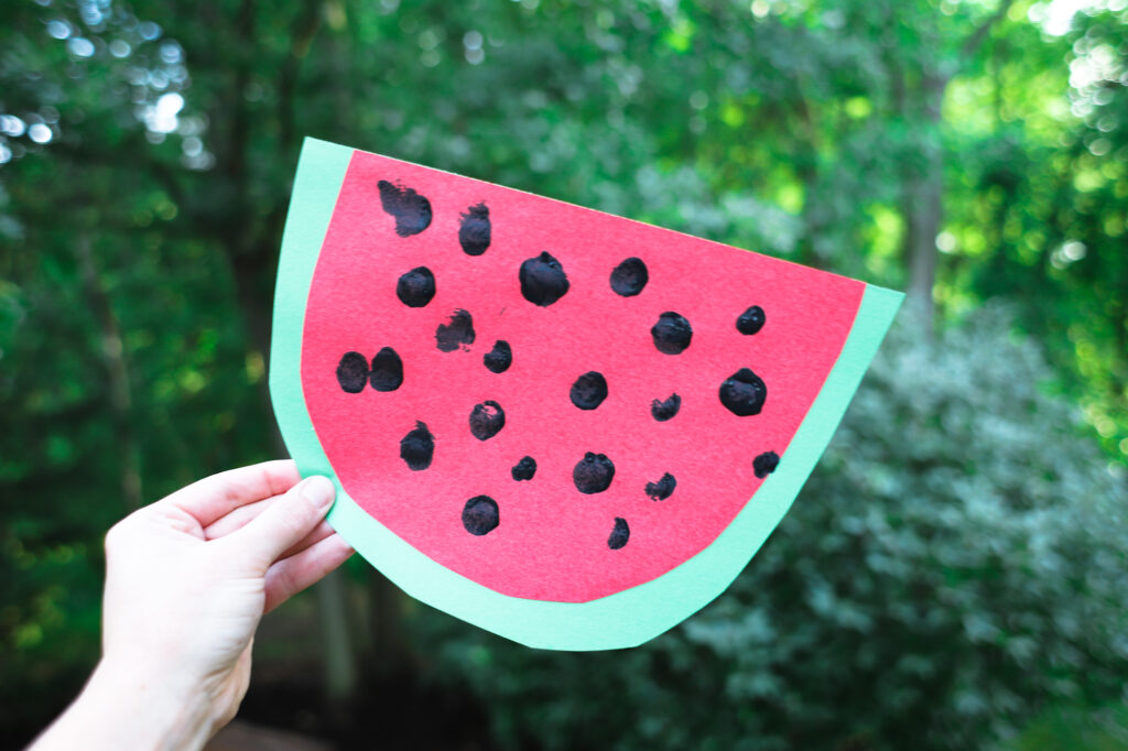 Picture of construction paper watermelon with black dot seeds.