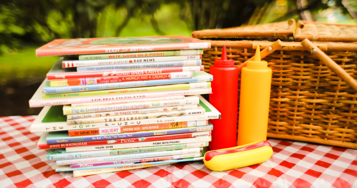 Pile of Picnic Picture Books Next to Picnic Basket and hotdog