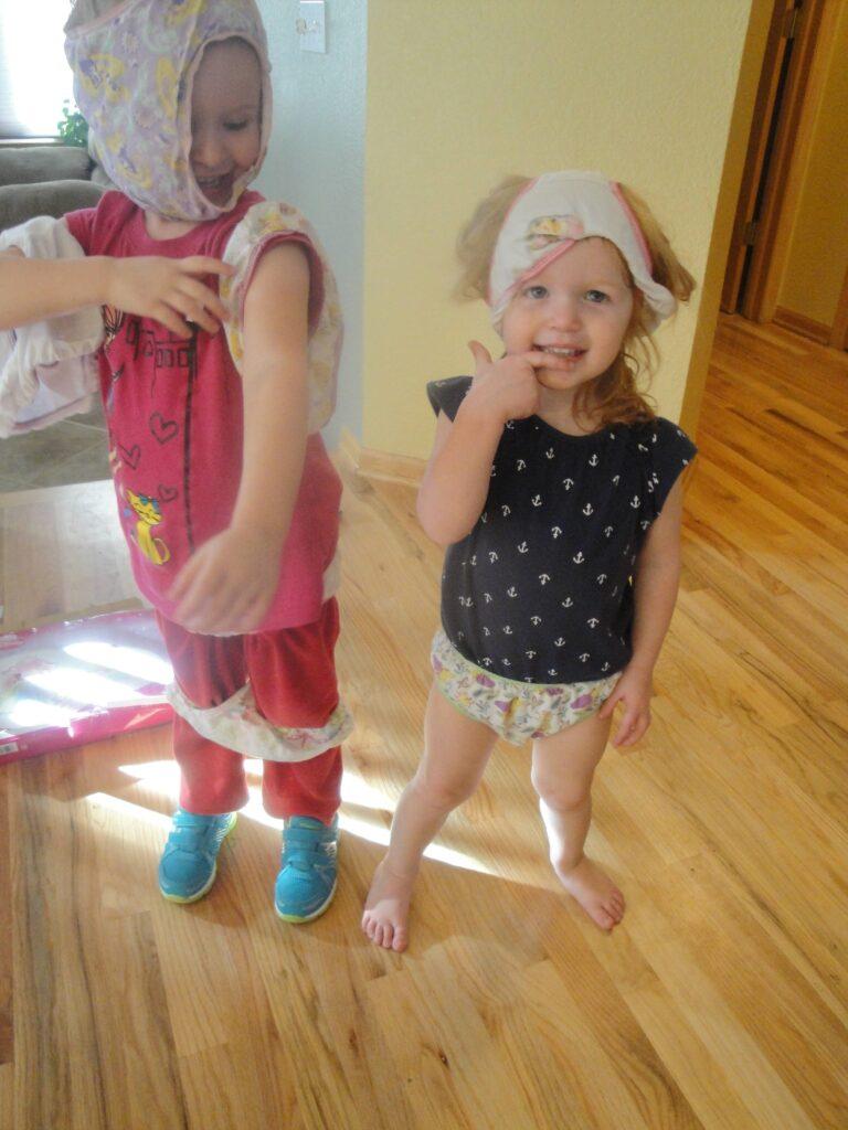 Two girls playing dress-ups in underwear.