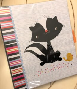 Binder with skunk on the front.