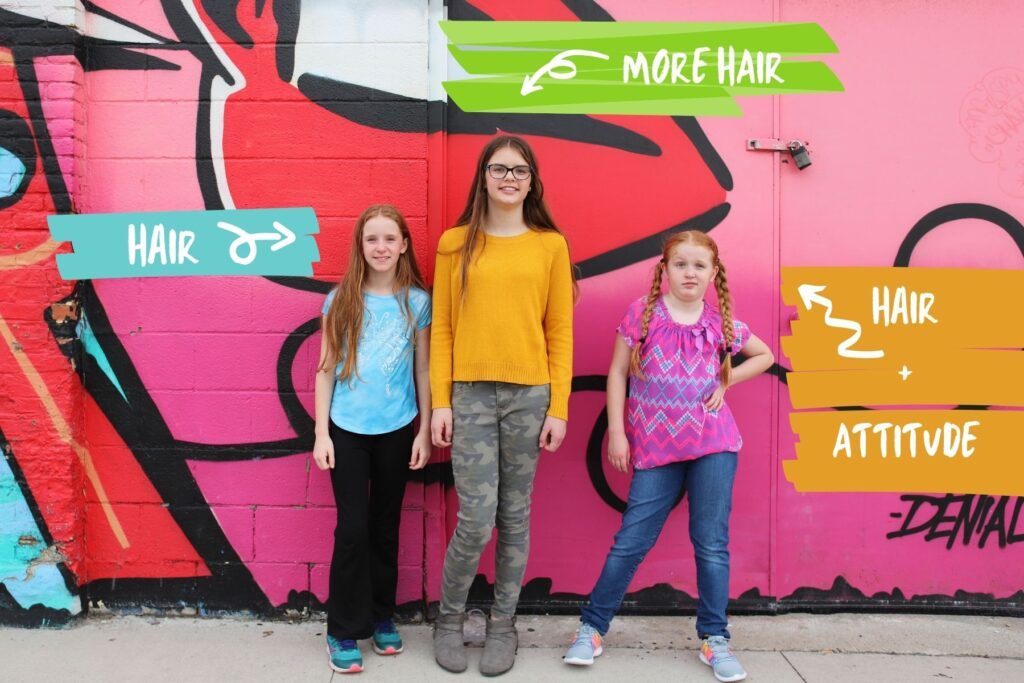 Three girls in front of a tagged wall.